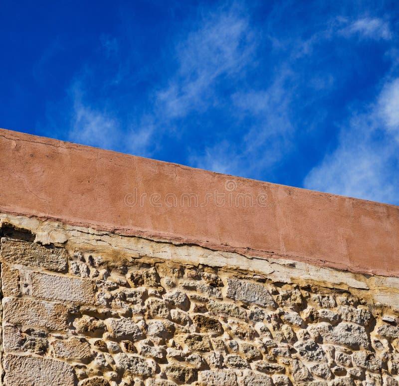 Blauwe hemel en oranje details van een oud gebouw - concrete en oude baksteen stock foto's