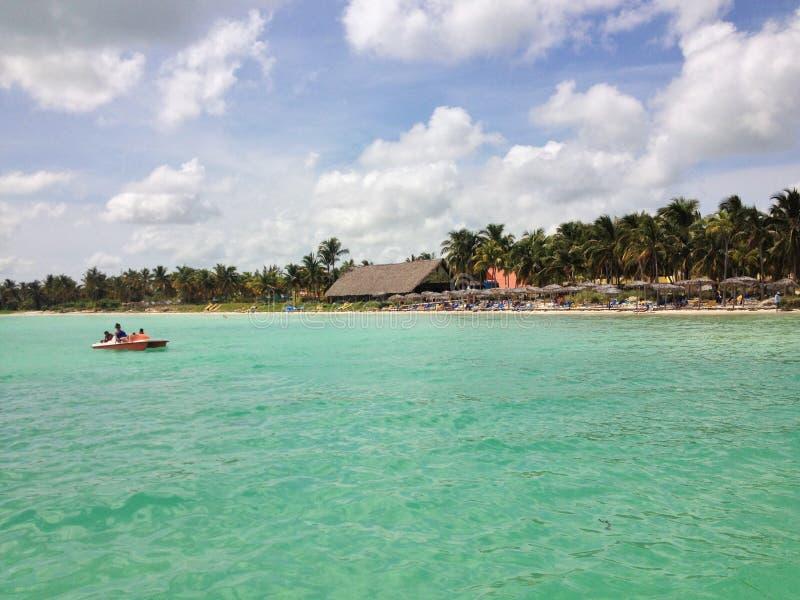 Blauwe hemel en wolken over een mooi tropisch strand met groene palmen en vreedzaam kristal turkoois water Cayo Guilermo, Cuba stock foto's