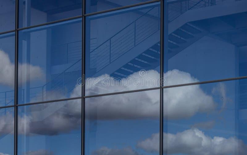 Blauwe hemel en wolkenbezinning in de bureaubouw venster stock fotografie
