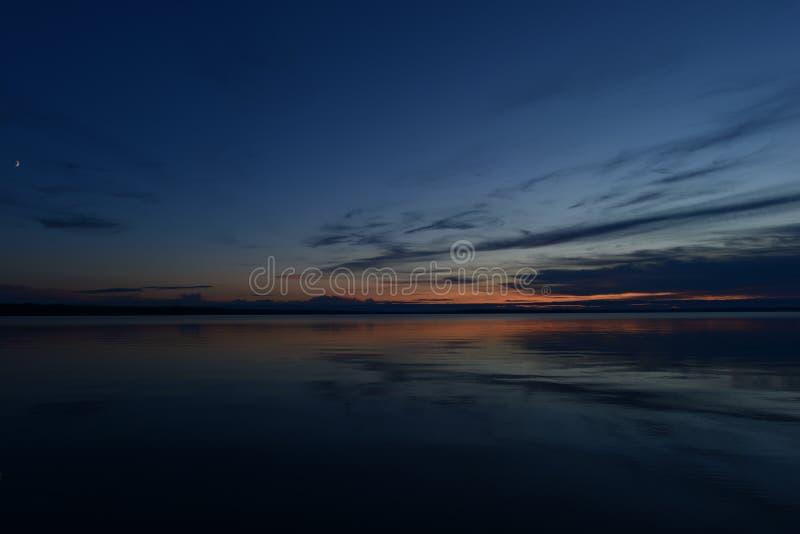 Blauwe hemel in het licht en de schaduwen van schemering bij het toenemen van de maan in de stilte van het water van het meer royalty-vrije stock foto