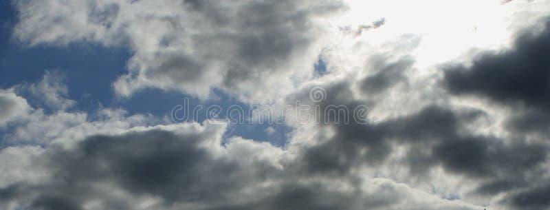 Blauwe hemel met pluizige witte en grijze wolken, zon die door glanzen stock fotografie
