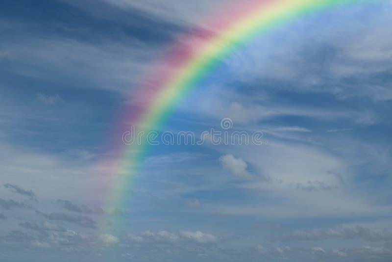 Blauwe hemel met regenboog stock afbeeldingen