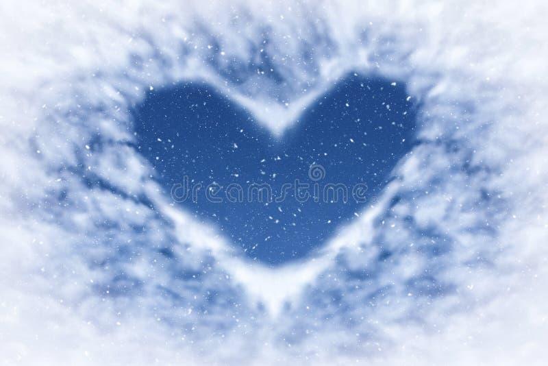 Blauwe hemel met sneeuw en wolken in hartvorm Gelukkige en liefdeachtergrond royalty-vrije stock fotografie