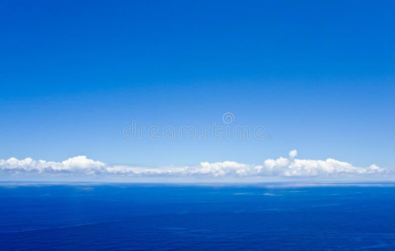 Blauwe hemel met sommige witte wolken boven de Atlantische Oceaan stock foto's