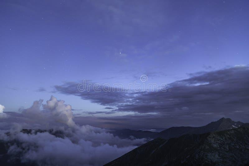 blauwe hemel met sterren en wolken boven een berg royalty-vrije stock foto