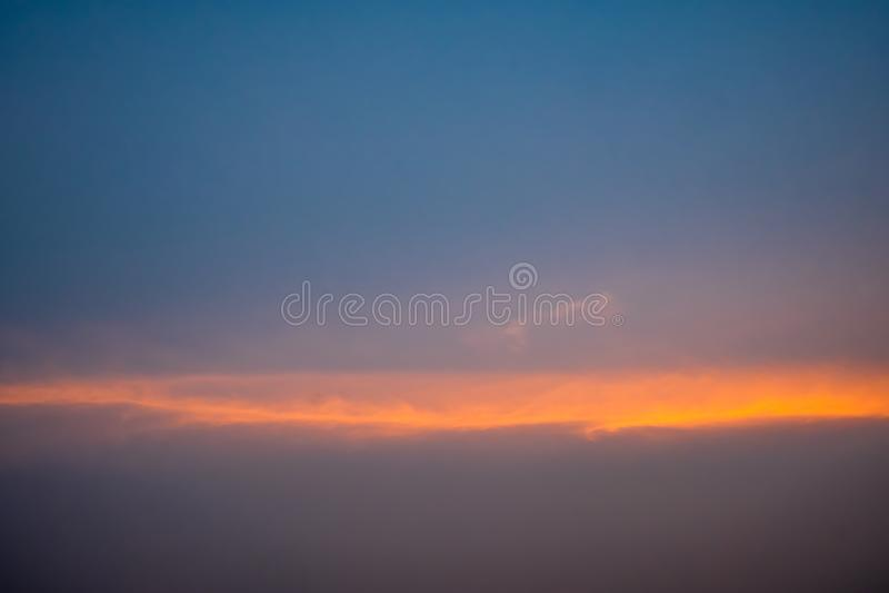 Blauwe hemel met witte pluizige wolken, oranje stralen van licht horizontaal tijdens zonsondergang stock afbeeldingen