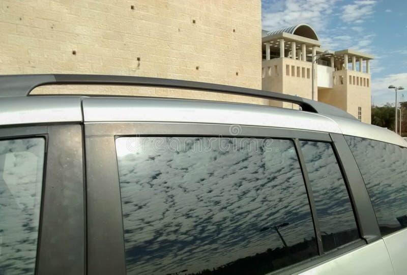 Blauwe hemel met witte wolken, die in venster van auto nadenken stock foto's