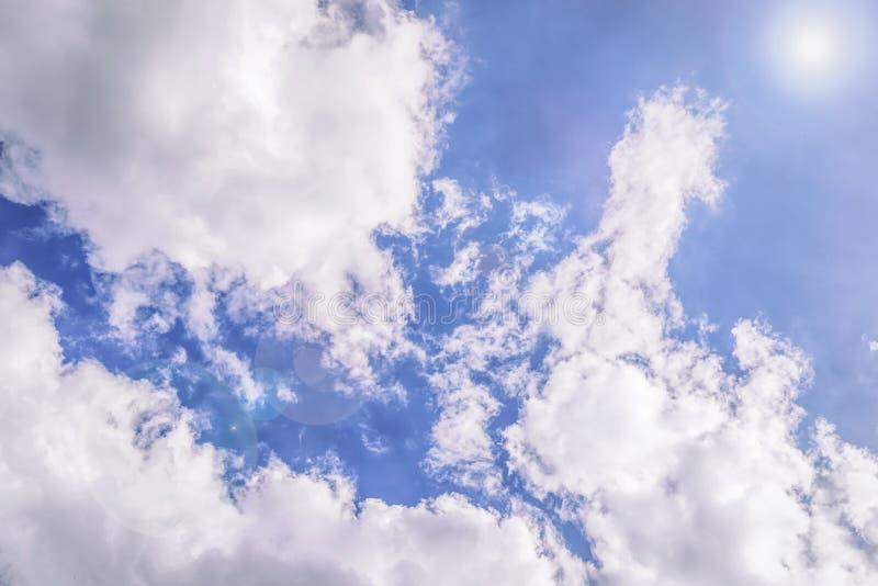 Blauwe hemel met witte wolken en zonglans De achtergrond van de hemel Gestemde foto stock foto