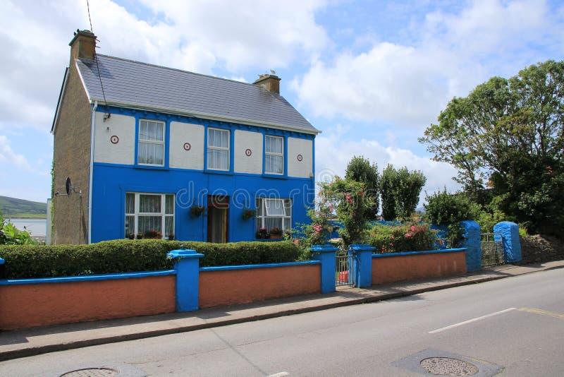 Blauwe hemel met wolken en een opvallend blauw huis in dorpsdingle in provincie Kerry in Ierland in de zomer stock foto