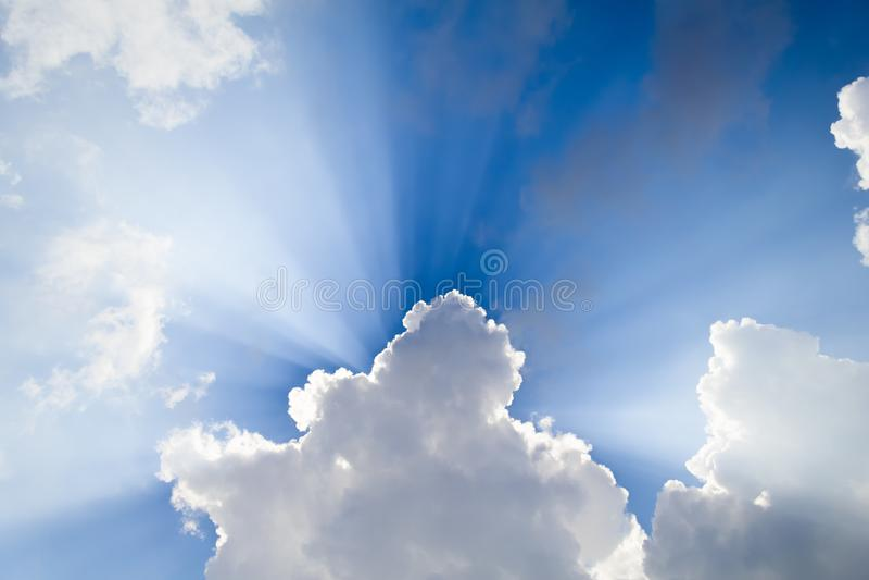 Blauwe hemel met zonnebalken en wolken stock afbeeldingen