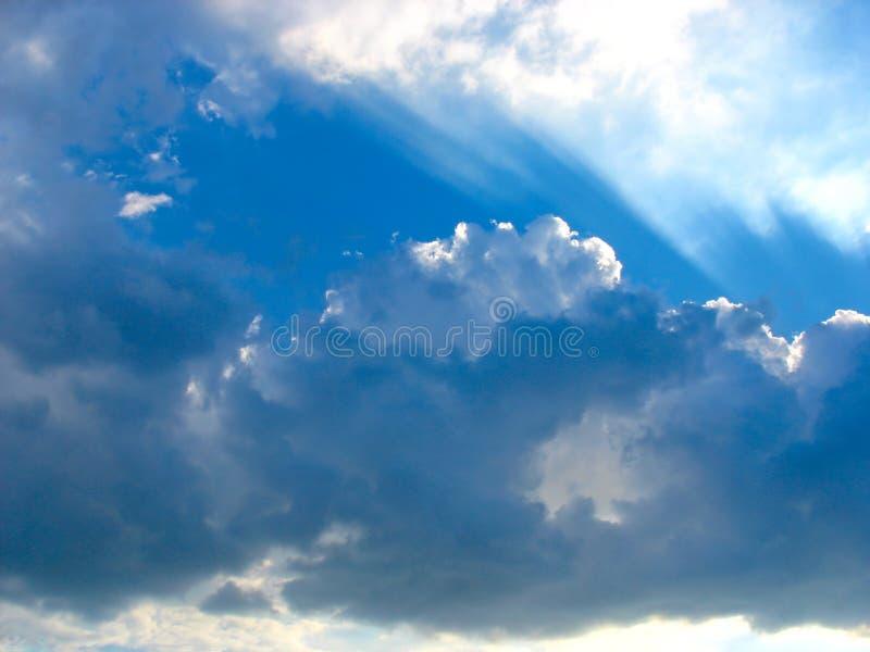 Blauwe hemel met zonstralen door de wolken stock afbeelding