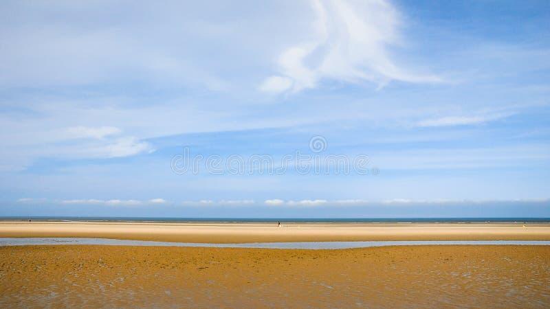 Blauwe hemel over nat geel zandstrand Le Touquet royalty-vrije stock fotografie