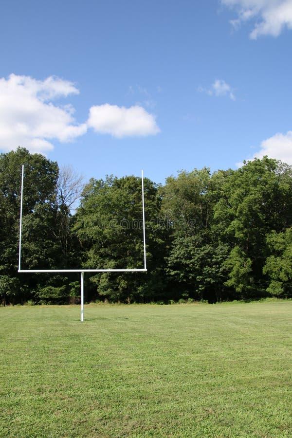 Blauwe hemel in rug van de doelpost op het voetbalgebied stock foto