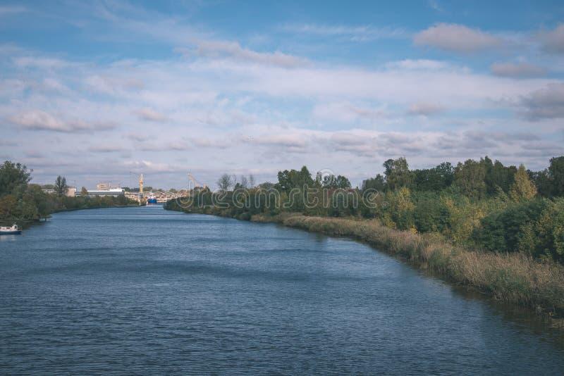 blauwe hemel, wolken en bomen van bos die in kalm meerwater nadenken - uitstekende retro ziet eruit royalty-vrije stock afbeelding