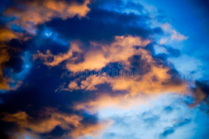 Blauwe hemelachtergrond met Oranje Wolken stock foto