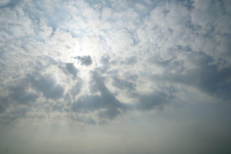 Blauwe hemelachtergrond met witte wolken en zonstraal stock foto