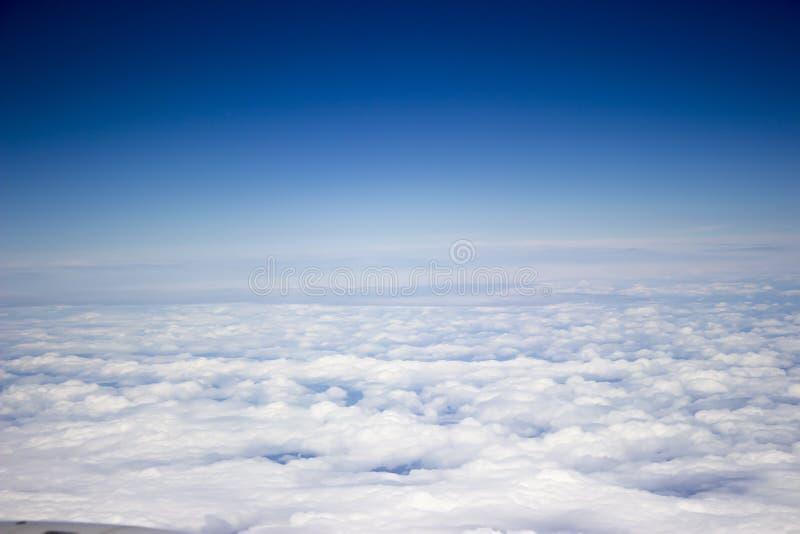 Blauwe hemelmening als achtergrond van vliegtuig omhoog dan de wolken in een zonnige dag royalty-vrije stock foto