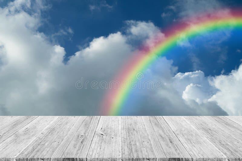 Blauwe hemelwolk met Houten terras en regenboog stock afbeelding