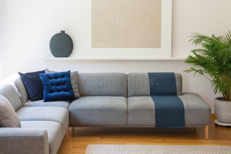 Blauwe hoofdkussens op grijze hoeklaag in woonkamerbinnenland met p royalty-vrije stock afbeeldingen