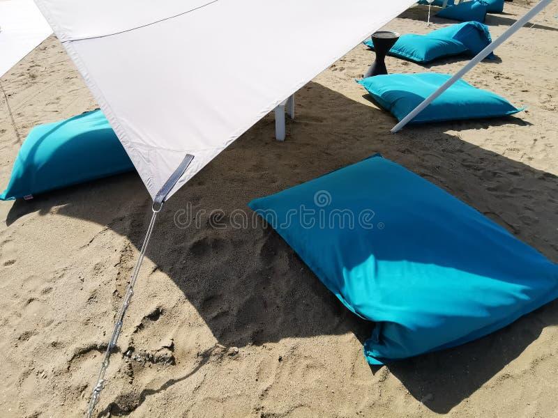 Blauwe hoofdkussens op het strand en de witte paraplu royalty-vrije stock afbeeldingen