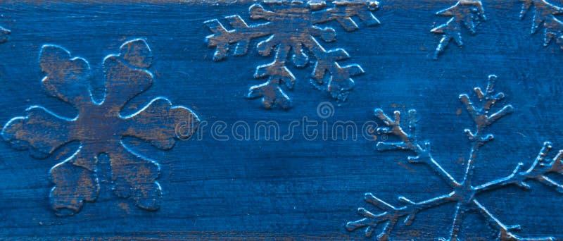 Blauwe houten achtergrond met zilveren sneeuwvlokken stock afbeeldingen