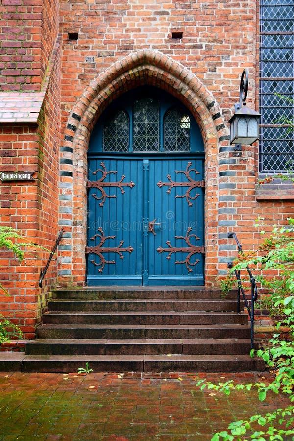 Blauwe houten deur, ingang aan een oude baksteenkerk stock fotografie