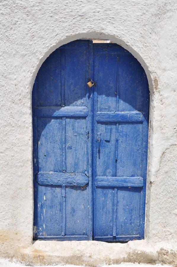 Blauwe houten deur op santorinieiland, Griekenland stock foto