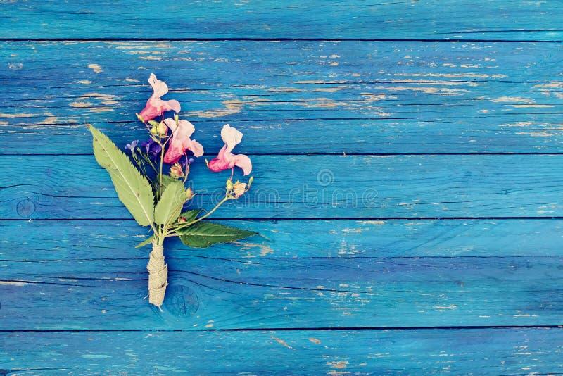 Blauwe houten textuur met klein boeket van Indische balsembloemen De installatie van Impatiensglandulifera Natuurlijke houten raa stock afbeeldingen