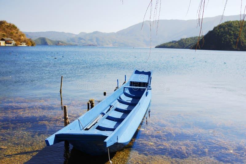 Blauwe houten vissersboot die op blauwe het meer toneeldievlek drijven van waterlugu door sneeuwberg en hoge hemel wordt omringd stock afbeelding