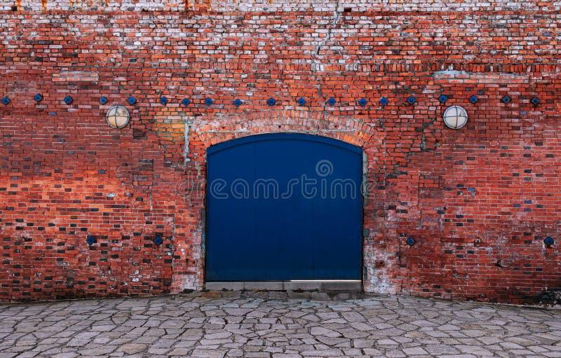 Blauwe ijzerpoort met rode bakstenen wand oude loft warehouse stock foto