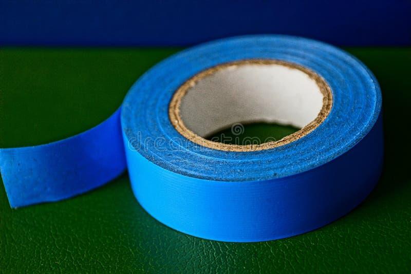 Blauwe industriële isolerende band op een groene oppervlakte royalty-vrije stock fotografie