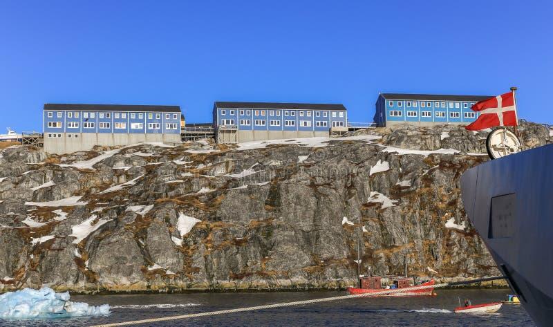 Blauwe Inuit-huizen op de rots langs de fjord met schip en boot royalty-vrije stock afbeeldingen