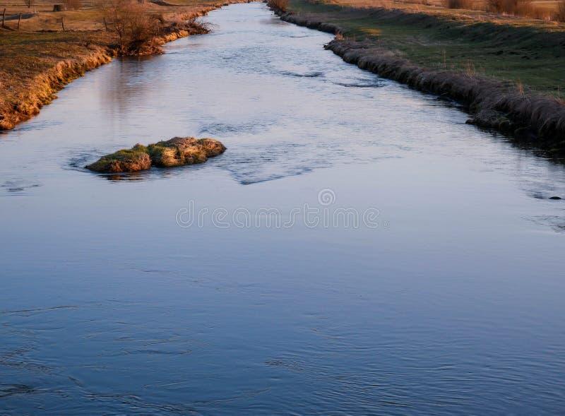 Blauwe, kalme, vuile Olt-rivier bij zonsondergang in de lente in Transsylvanië royalty-vrije stock afbeeldingen