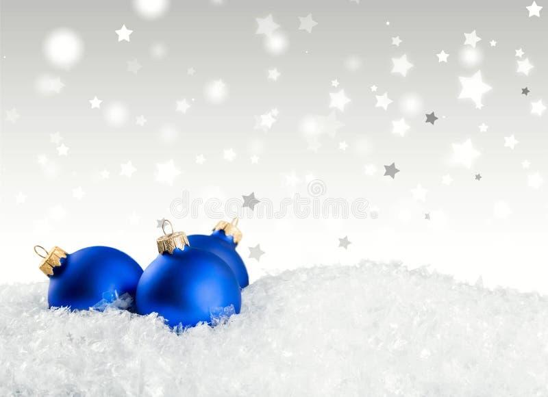 Blauwe Kerstmisballen op sneeuwachtergrond stock illustratie