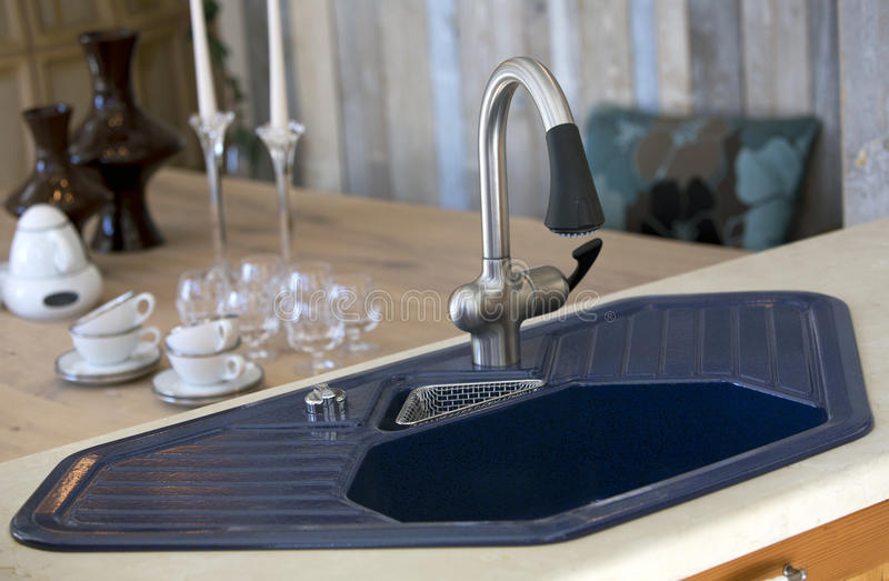Blauwe keukengootsteen en eetkamerlijst met schotels stock foto's