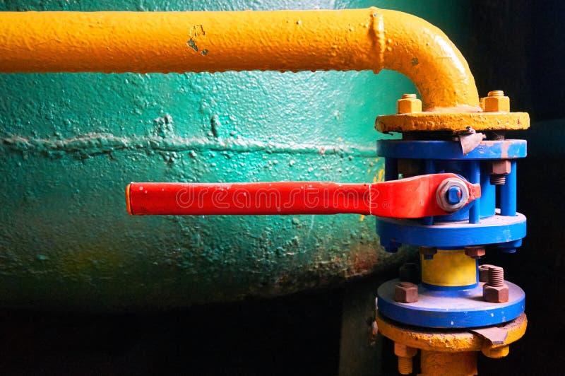 Blauwe klep met een rood die handvat op de waterpijp, in geel wordt geschilderd abstracte achtergrond royalty-vrije stock fotografie