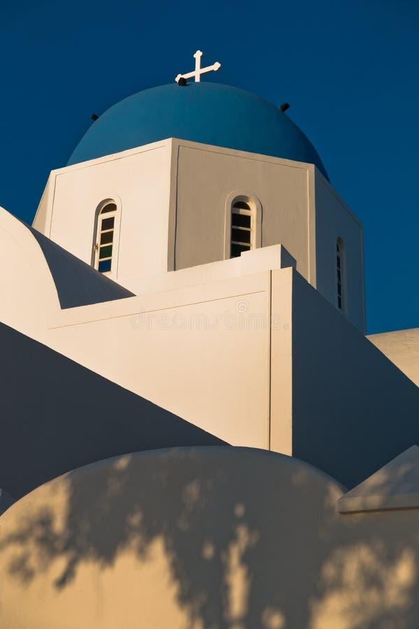 Blauwe koepel van een witte kerk bij zonsondergang, Oia dorp, Santorini-eiland stock fotografie