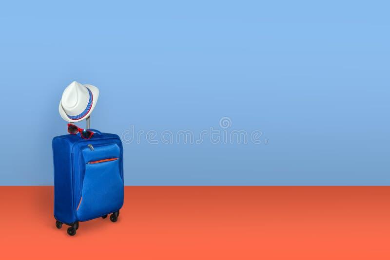 Blauwe koffer met een de zomerhoed en modieuze glazen op lichtblauwe/oranje achtergrond, een concept van de de zomervakantie, vri royalty-vrije stock foto