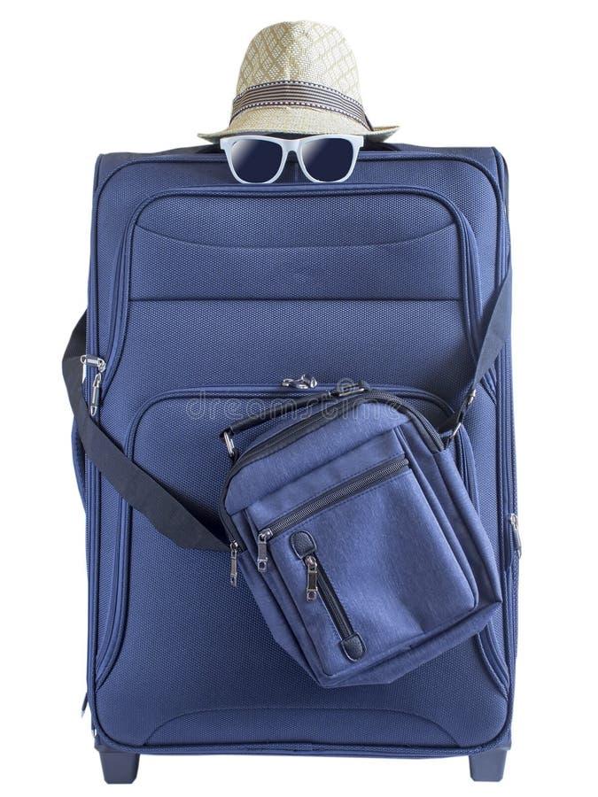 Blauwe koffer met een de zomerhoed en modieuze glazen op lichte witte achtergrond De achtergrond van de reis stock foto