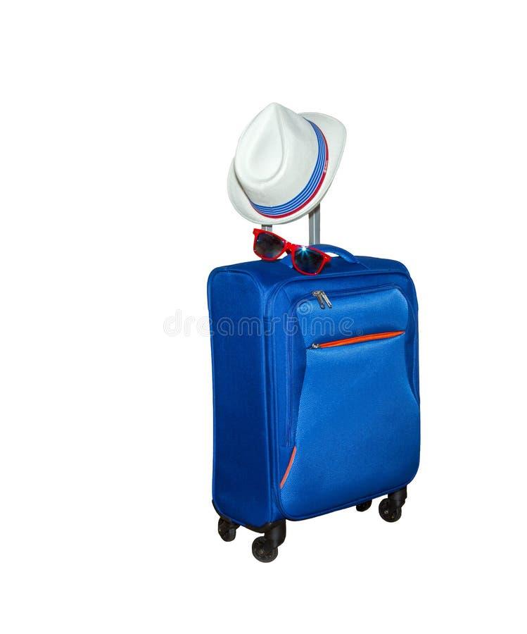 Blauwe koffer met een de zomerhoed en modieuze zonnebril op witte achtergrond De reisconcept van de de zomervakantie royalty-vrije stock fotografie