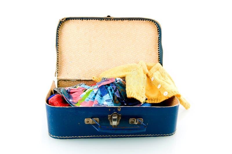 Blauwe koffer met kleren stock foto