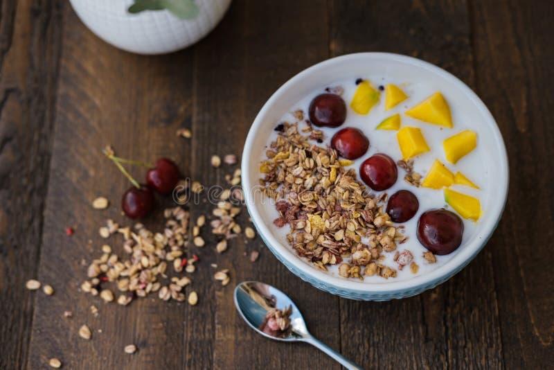 Blauwe Kom van eigengemaakte die Granola met yoghurt en verse berrie wordt gebakken royalty-vrije stock afbeelding