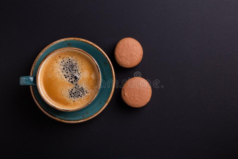 Blauwe kop koffie en makarons op de donkere houten lijst De onderbreking van Coffe stock afbeeldingen