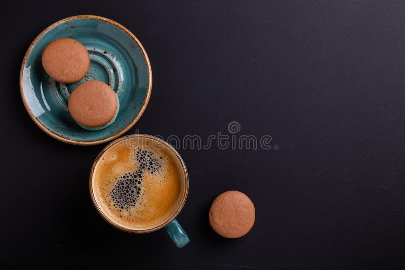 Blauwe kop koffie en makarons op de donkere houten lijst De onderbreking van Coffe royalty-vrije stock fotografie