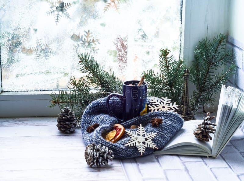 Blauwe kop met thee en open boek op de achtergrond van venster met de winterpatroon Het concept comfortabel decor royalty-vrije stock afbeelding