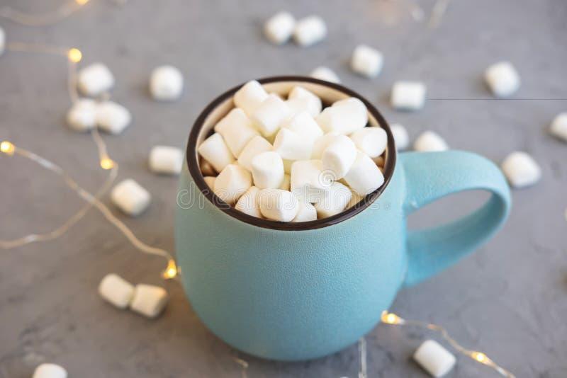 Blauwe kop van koffie op grijze concrete achtergrond met heemst en slinger De comfortabel drankherfst en de winterconcept stock foto's