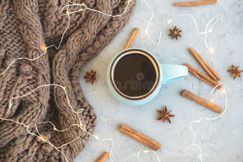 Blauwe kop van koffie op grijze concrete achtergrond Warme sjaal, pijpjes kaneel, anijsplantsterren en slinger De comfortabele dr royalty-vrije stock foto's