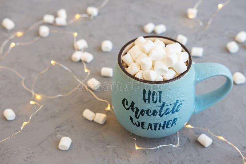 Blauwe kop van koffie op grijze concrete backgroundwith marsmallow en slinger Inschrijving op weer van de mok het Hete chocolade royalty-vrije stock foto