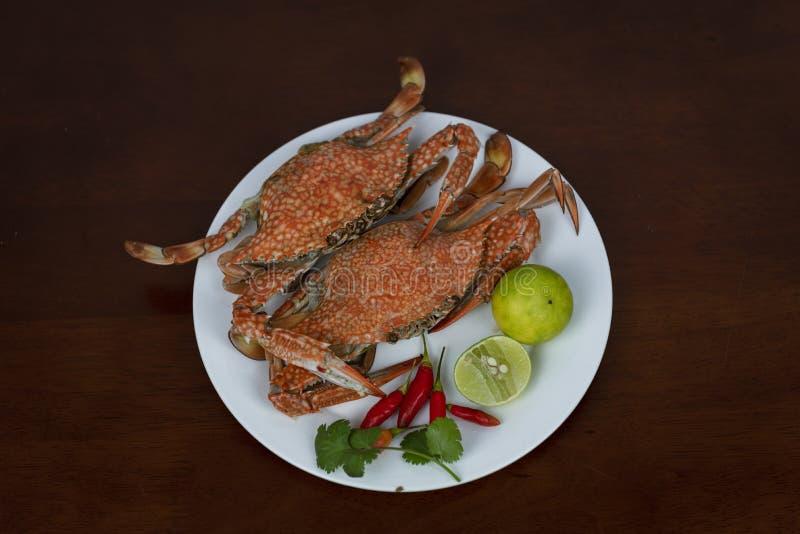 Blauwe krabben met Thaise zeevruchten onderdompelende saus op een plaat, op een hout royalty-vrije stock afbeelding