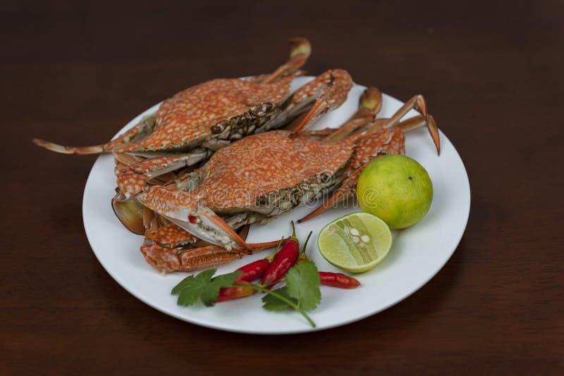 Blauwe krabben met Thaise zeevruchten onderdompelende saus op een plaat, op een hout stock fotografie